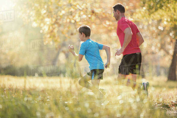 Father and son jogging in park Royalty-free stock photo