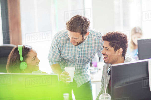 Creative business people with headphones and coffee laughing at computers Royalty-free stock photo