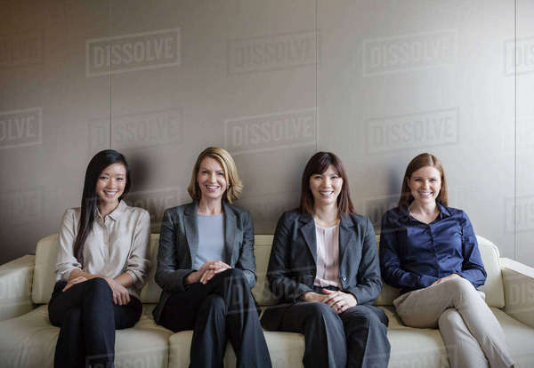 Portrait smiling businesswomen sitting in a row on sofa Royalty-free stock photo