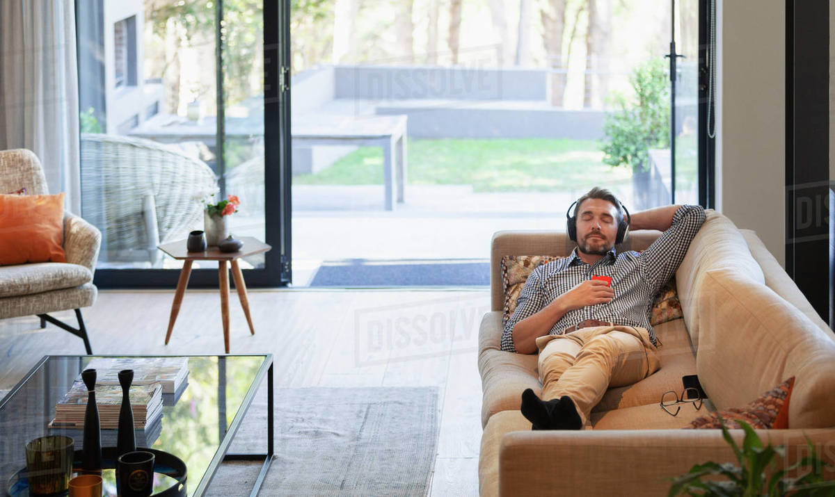 Man relaxing on living room sofa, listening to music with headphones and mp3 player Royalty-free stock photo