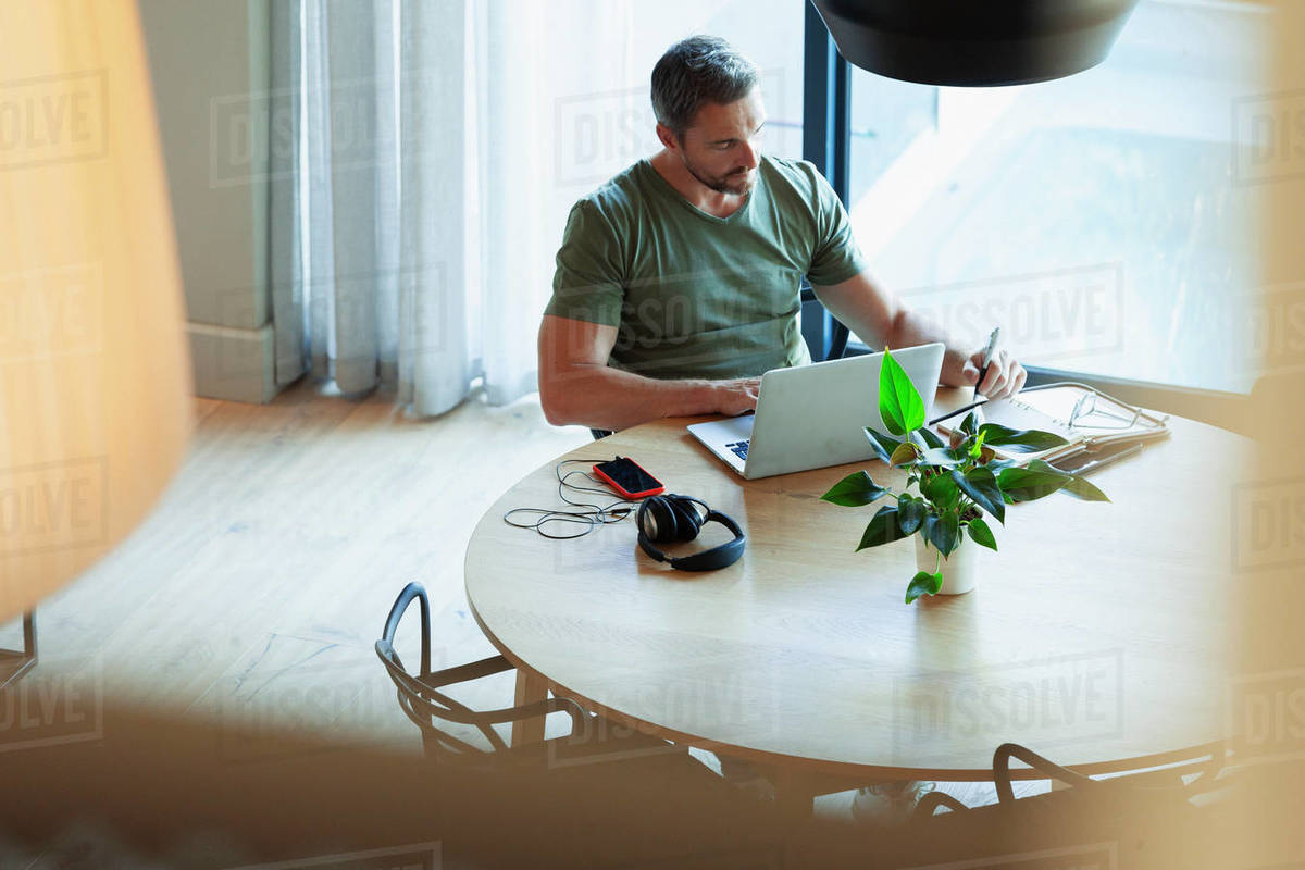 Man using laptop, working from home at dining table Royalty-free stock photo