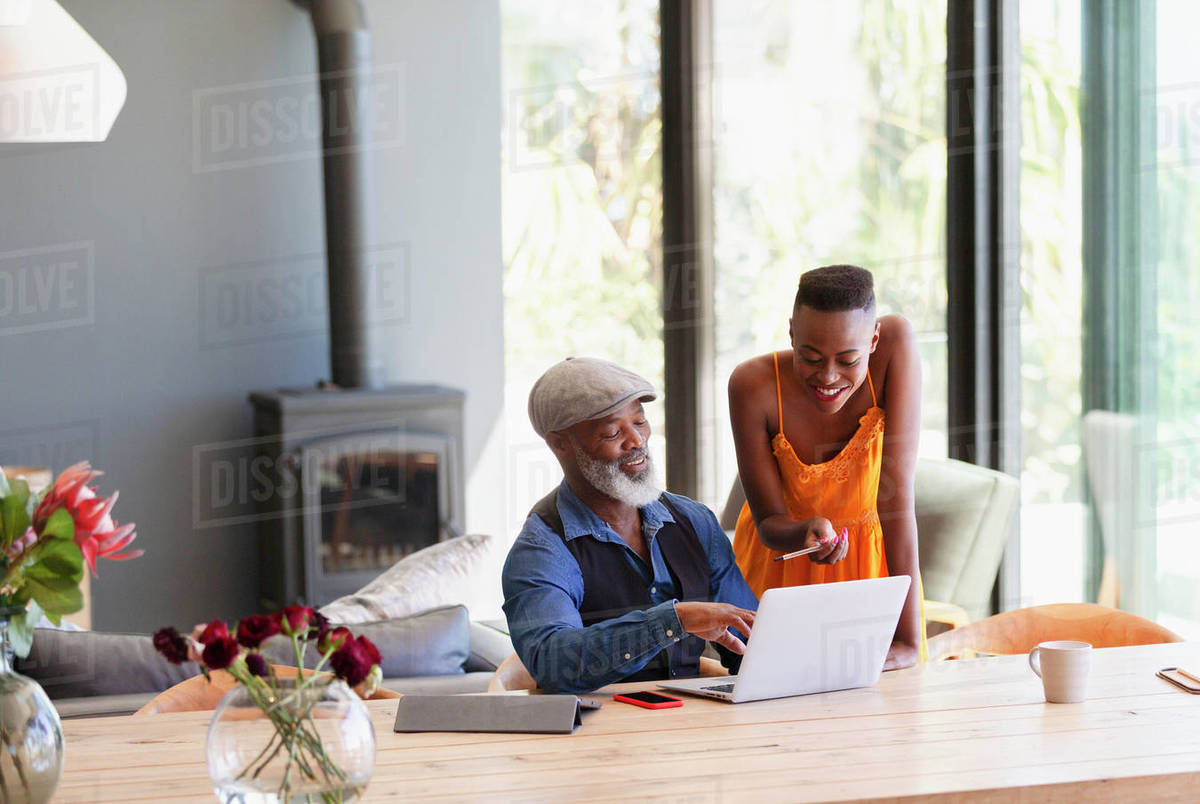 Father and daughter using laptop at dining table Royalty-free stock photo