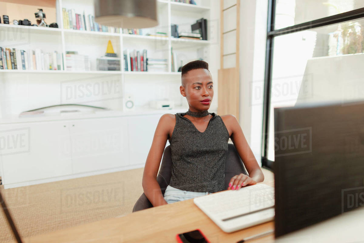 Young woman working from home, using computer in office Royalty-free stock photo