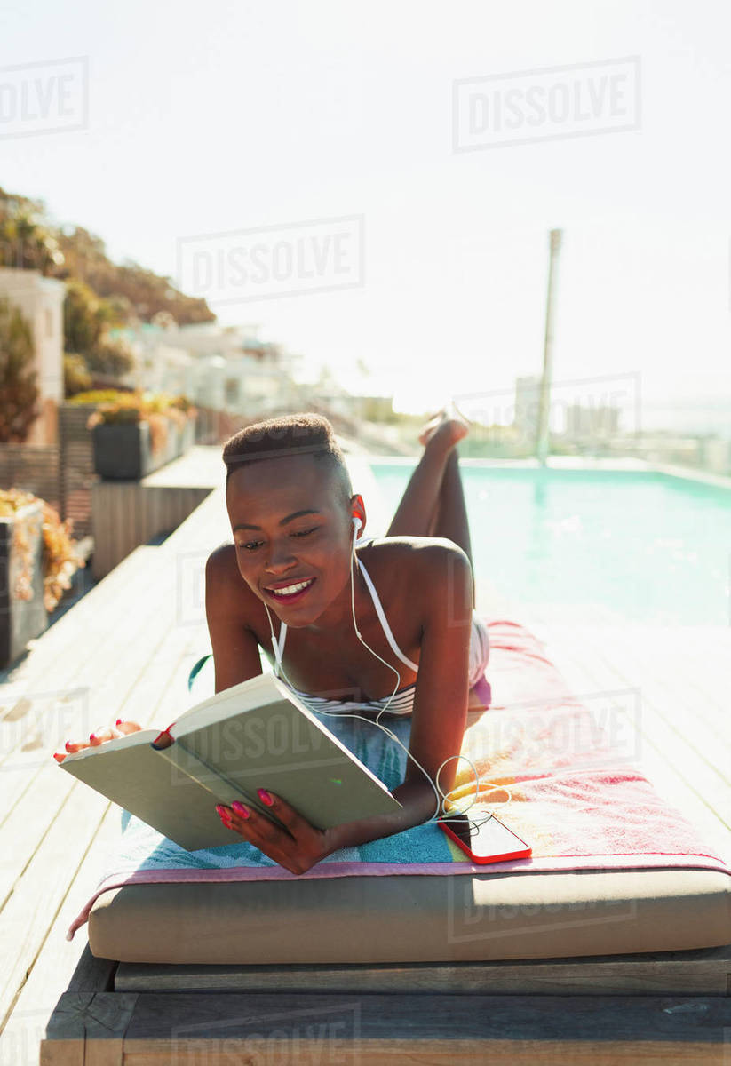 Woman sunbathing, reading book on sunny lounge chair at poolside Royalty-free stock photo