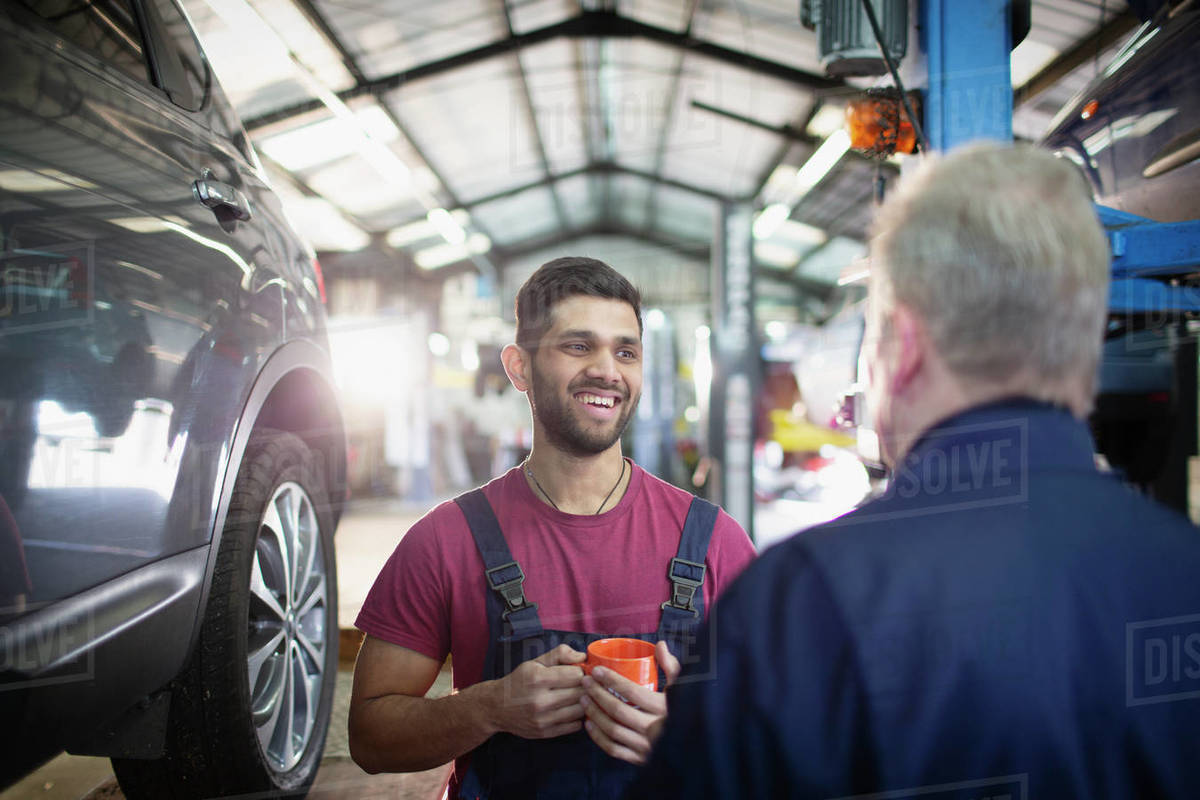 Smiling, happy male mechanics talking and drinking coffee in auto repair shop Royalty-free stock photo