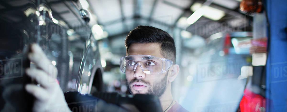 Focused male mechanic examining car in auto repair shop Royalty-free stock photo