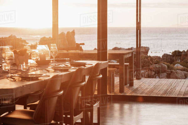 Sunny home showcase dining room overlooking ocean at sunset Royalty-free stock photo