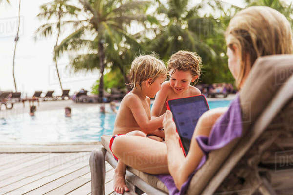 Mother and sons relaxing with digital tablet at poolside Royalty-free stock photo