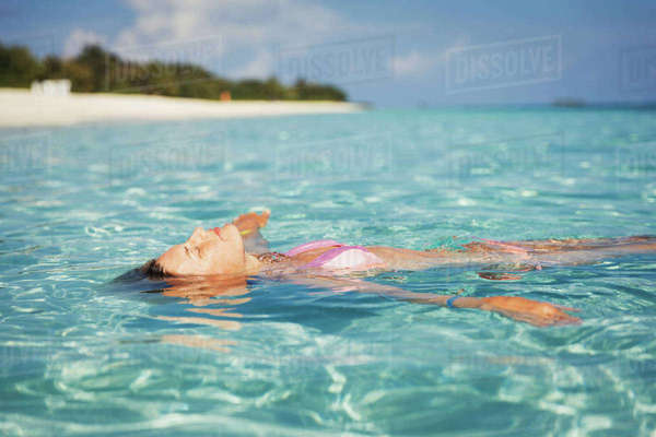 Serene woman floating in tropical ocean Royalty-free stock photo