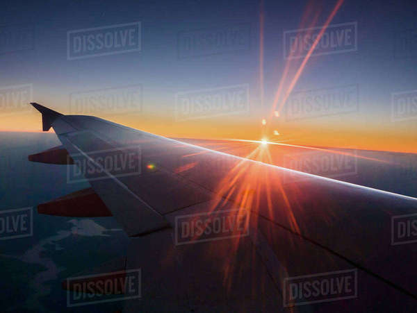 Sunset behind airplane wing in sky Royalty-free stock photo