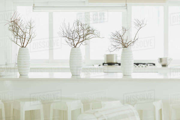 Modern white dining table with white vases and branches Royalty-free stock photo