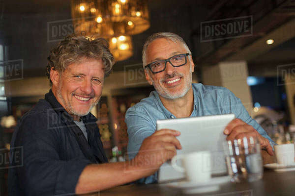 Portrait smiling men using digital tablet and drinking coffee at restaurant table Royalty-free stock photo