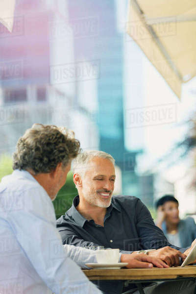 Businessmen using digital tablet at urban sidewalk cafe Royalty-free stock photo