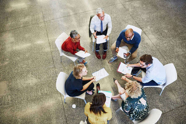 Business people discussing paperwork in meeting circle Royalty-free stock photo