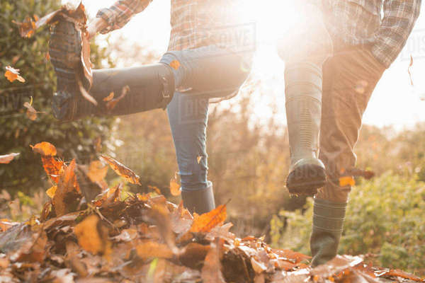 Couple in rain boots kicking autumn leaves Royalty-free stock photo