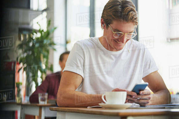Smiling man with headphones using cell phone and drinking coffee in cafe Royalty-free stock photo