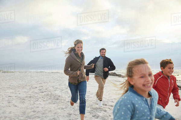 Playful family running on beach Royalty-free stock photo