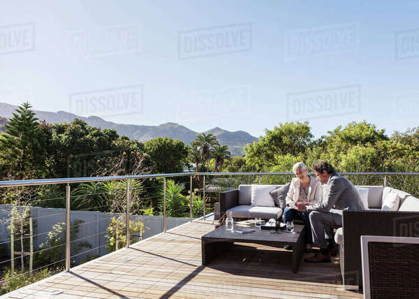Businessman and businesswoman working on sunny luxury balcony patio sofa Royalty-free stock photo