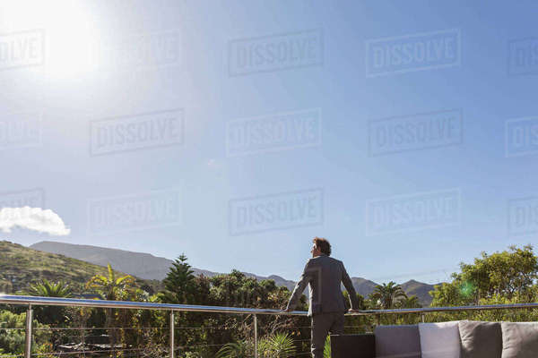 Businessman standing on balcony patio below sunny blue sky Royalty-free stock photo