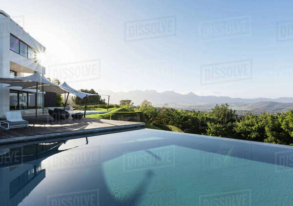 Tranquil, sunny home showcase exterior with infinity pool and mountain view under blue sky Royalty-free stock photo
