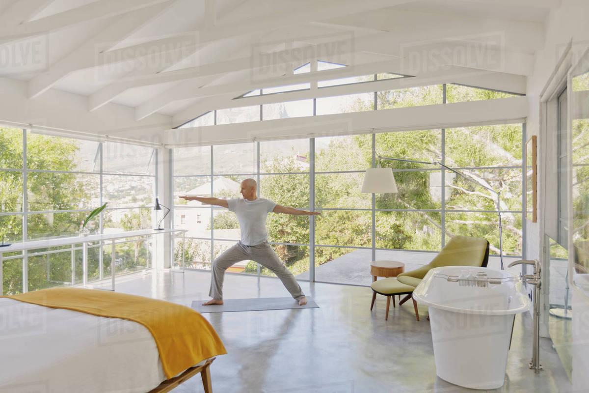 Mature Man Practicing Yoga Warrior 2 Pose In Luxury Bedroom Stock
