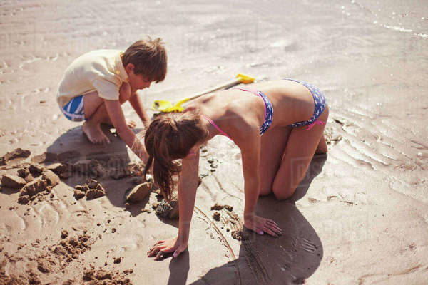 Brother and sister in bathing suit playing in wet sand on sunny summer beach Royalty-free stock photo