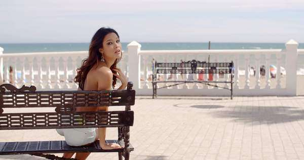 Happy young woman relaxing in the sun at the seaside sitting on a bench looking back at the camera with a teasing playful smile Royalty-free stock video