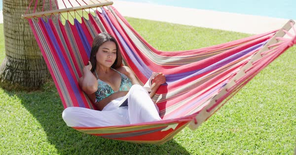 beautiful single young adult woman in bikini top and white pants seated  fortably in colorful hammock relaxing woman in bikini top and white pants seated in colorful      rh   dissolve
