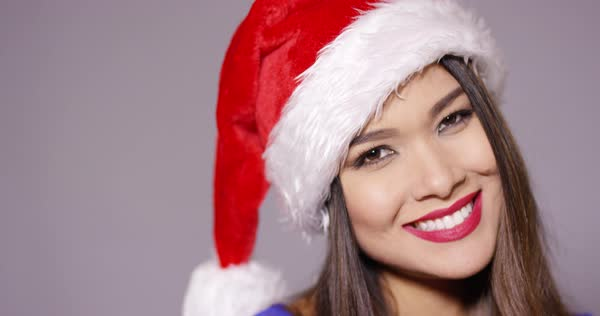 9b1c9e5156298 Sensuous young woman in a red Santa hat sucking on a colorful red and white  striped