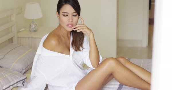 dead905273 Single beautiful young adult woman with sultry and seductive expression  sitting on bed Royalty-free