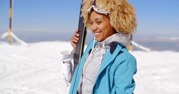 8cbc47c8ba Thoughtful young woman standing holding her skis and watching something off  frame to the left in