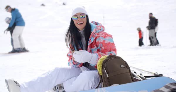 ae519492ec Happy young woman posing for a selfie in the snow as she sits relaxing with  her