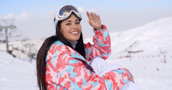 5d2042e939a Gorgeous young brunette woman in ski clothes and goggles sitting in the snow  at a mountain
