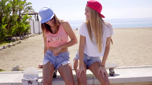 Two cute laughing young friends in shorts and hats sitting on skateboard near tropical beach along stone and concrete wall Royalty-free stock video