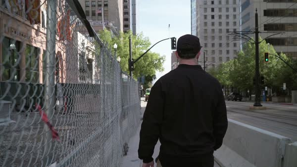 Medium shot of a man walking next to a fence Royalty-free stock video