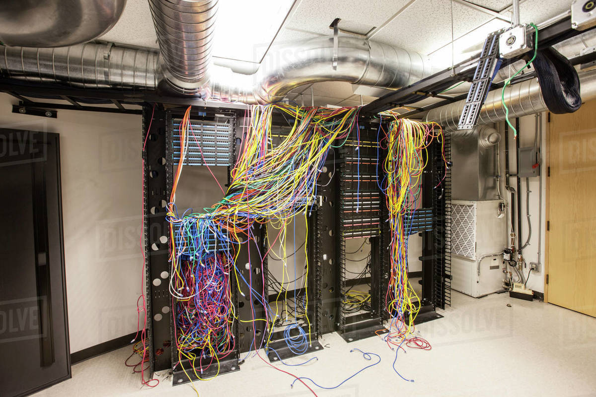 A mess of Cat 5 cables in an office server room  stock photo