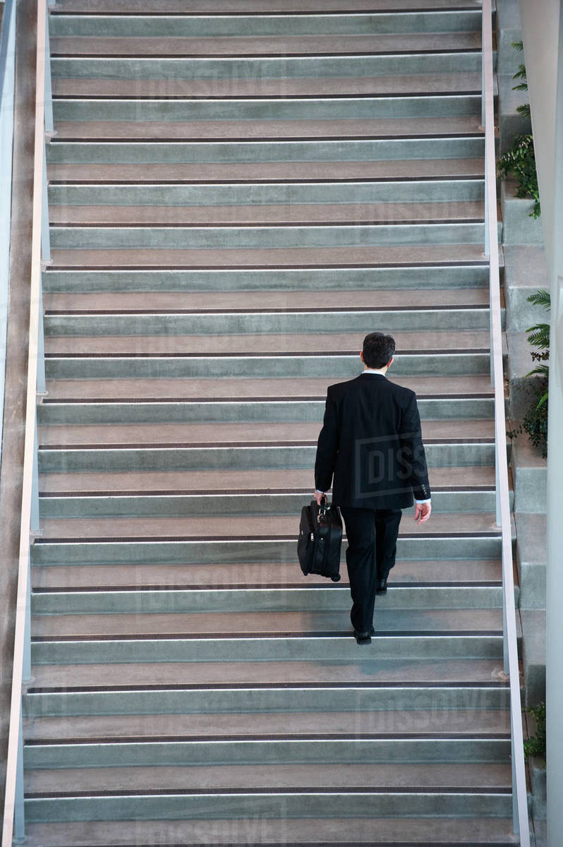 View From Above Looking Down On A Businessman Walking Up Stairs In A