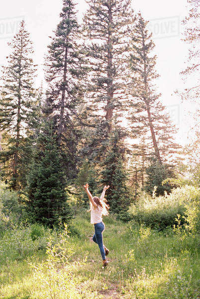 Woman jumping with joy in a sunlit forest. Royalty-free stock photo