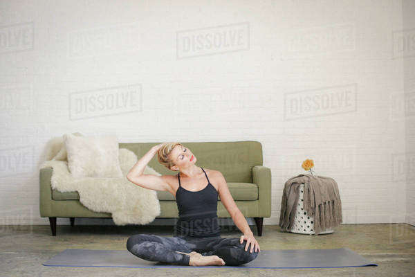 A blonde woman sitting on a yoga mat in a room. Royalty-free stock photo