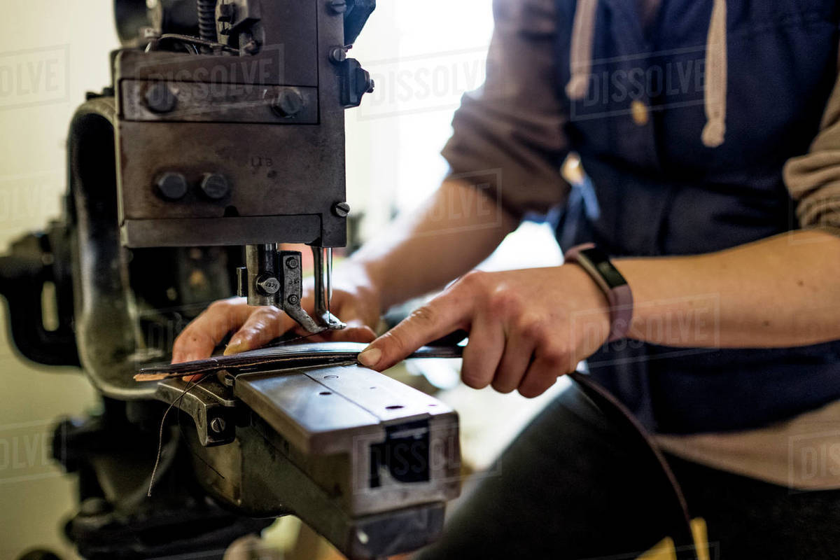 Female saddler standing in workshop, sewing leather strap on saddlery sewing machine. Royalty-free stock photo