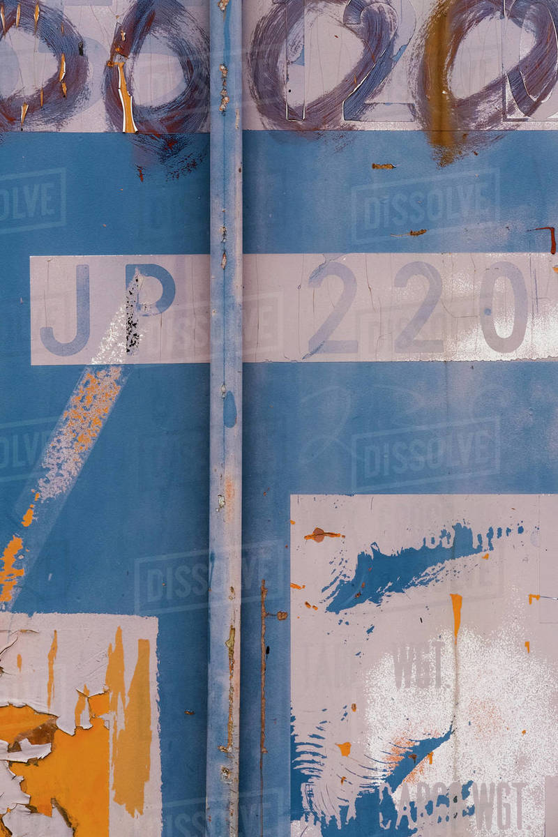 Detail of peeling paint and markings on colorfully painted industrial cargo container Royalty-free stock photo