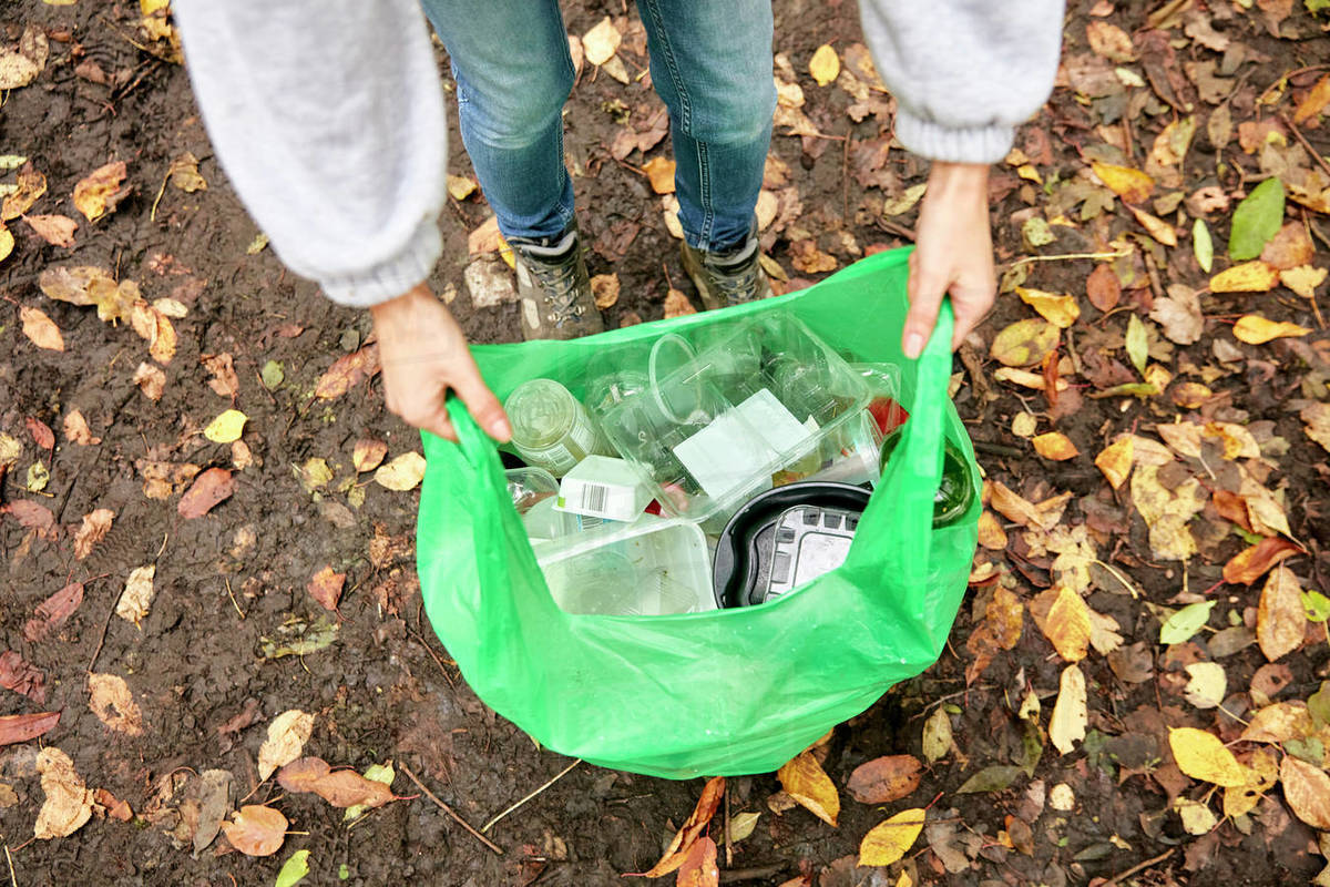 Plastic bag being held open filled with plastic litter Royalty-free stock photo