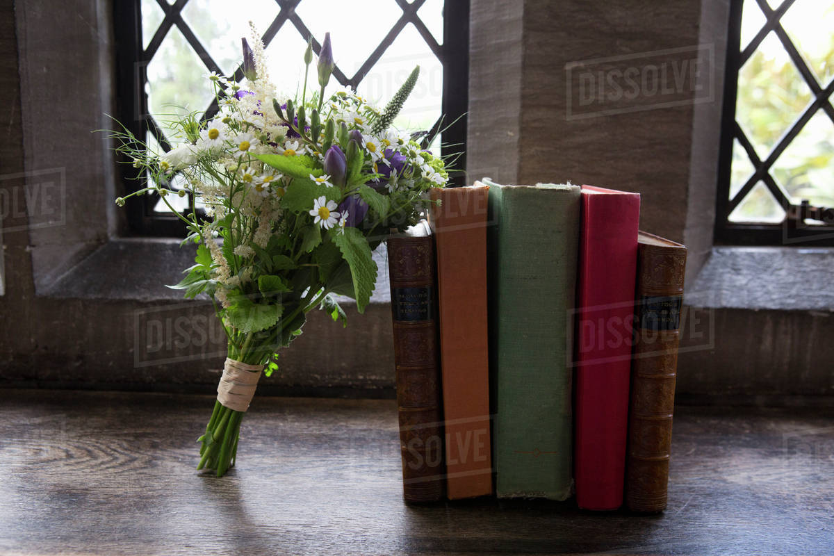 A Bouquet Of Blue And White Wedding Flowers Leaning Against Books