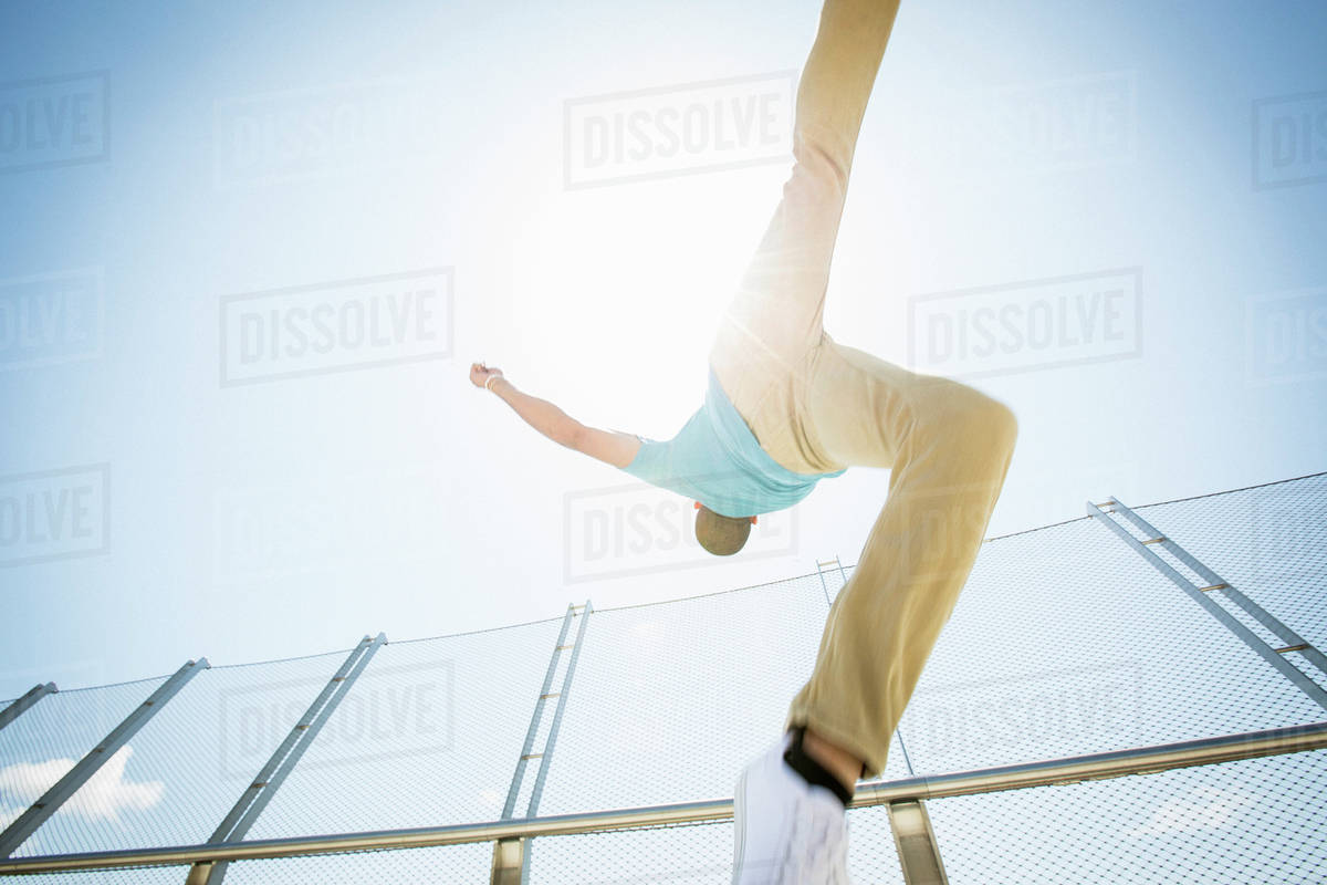 Young man somersaulting on a bridge.  Royalty-free stock photo