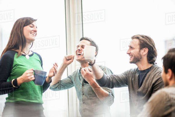 Four work colleagues on a break, laughing and raising their coffee cups. Royalty-free stock photo