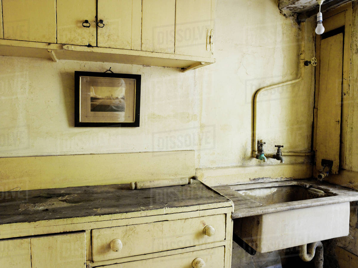 An Old Fashioned Kitchen Sink And Cupboards