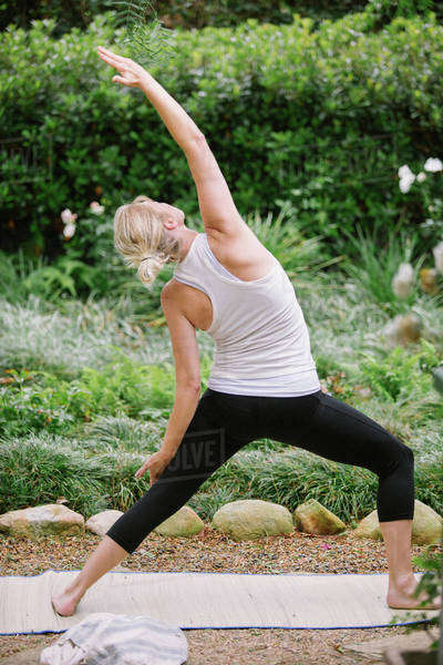 Blond woman doing yoga in a garden. Royalty-free stock photo