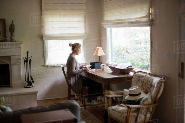 Blond woman sitting at a desk by a window, looking at photographs. Royalty-free stock photo