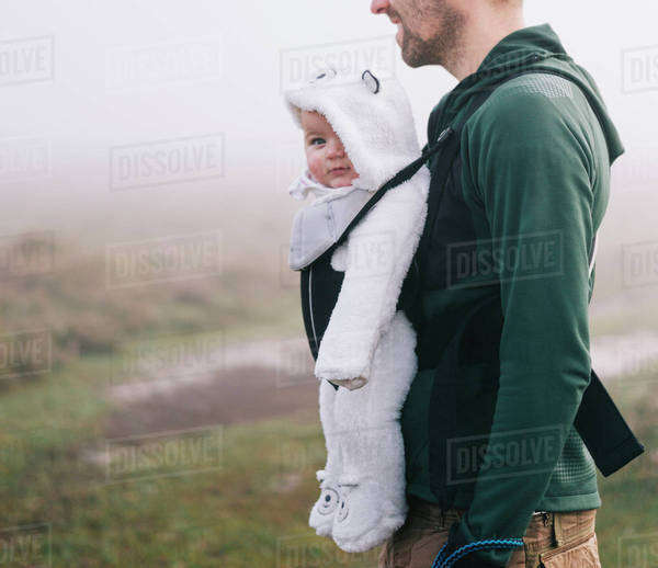 A man carrying a baby in a baby carrier on his chest, outdoors on a misty autumn day Royalty-free stock photo