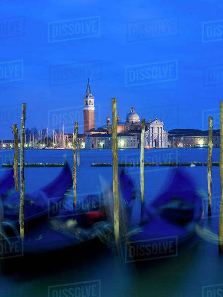 A view from the Riva degli Schiavoni and the Piazza San Marco across the water to the island and church of San Giorgio Maggiore. Gondolas moored at dusk. Royalty-free stock photo